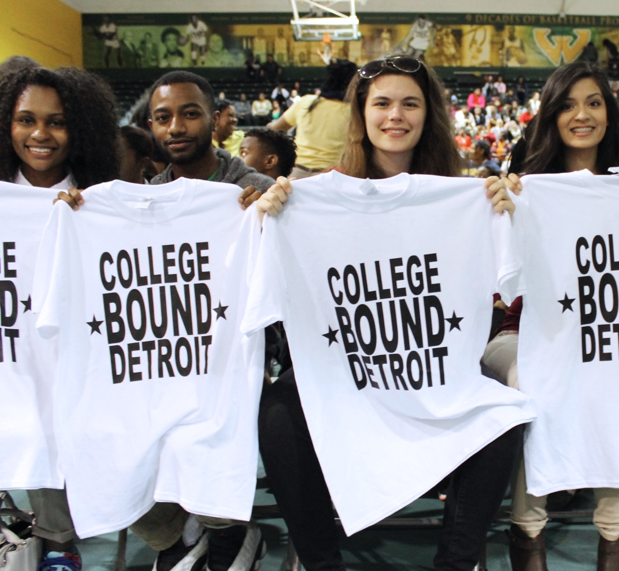 Students holding up College Bound Detroit T-Shirts